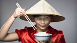 A young Asian girl comically lampooning an Asian stereotype - focus on the rice